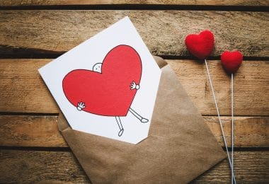 Envelope com uma carta sobre uma mesa de madeira, com um desenho de coração escrito.