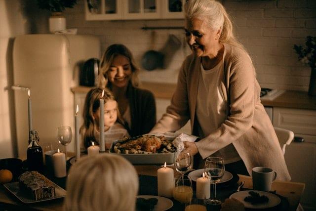 Mulher idosa colocando uma forma com um chester assado na mesa de jantar. Uma mulher com uma criança no colo sorri. Várias taças, copos e velas acesas estão na mesa.