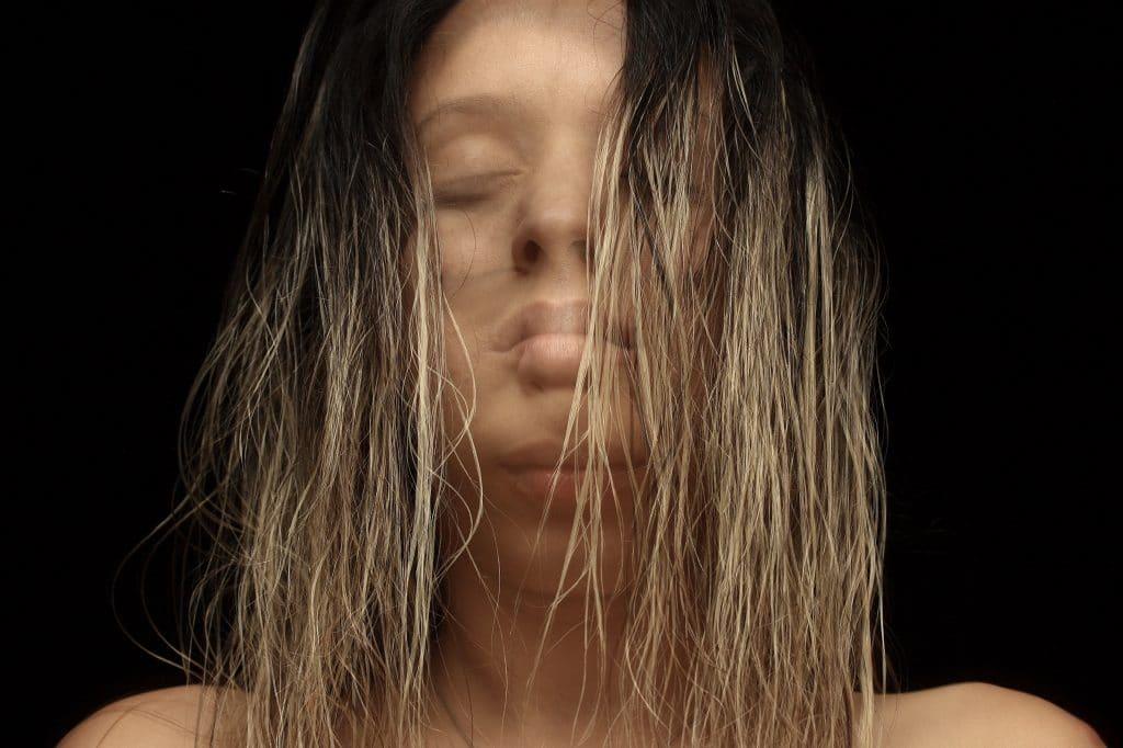 Mulher com imagem embaçada e duplicada de cabelos soltos e olhos fechados