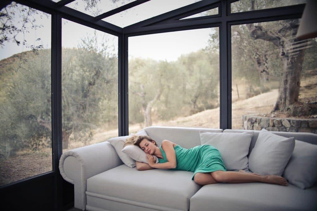 Mulher com vestido de festa verde cochilando em um sofá cinza.
