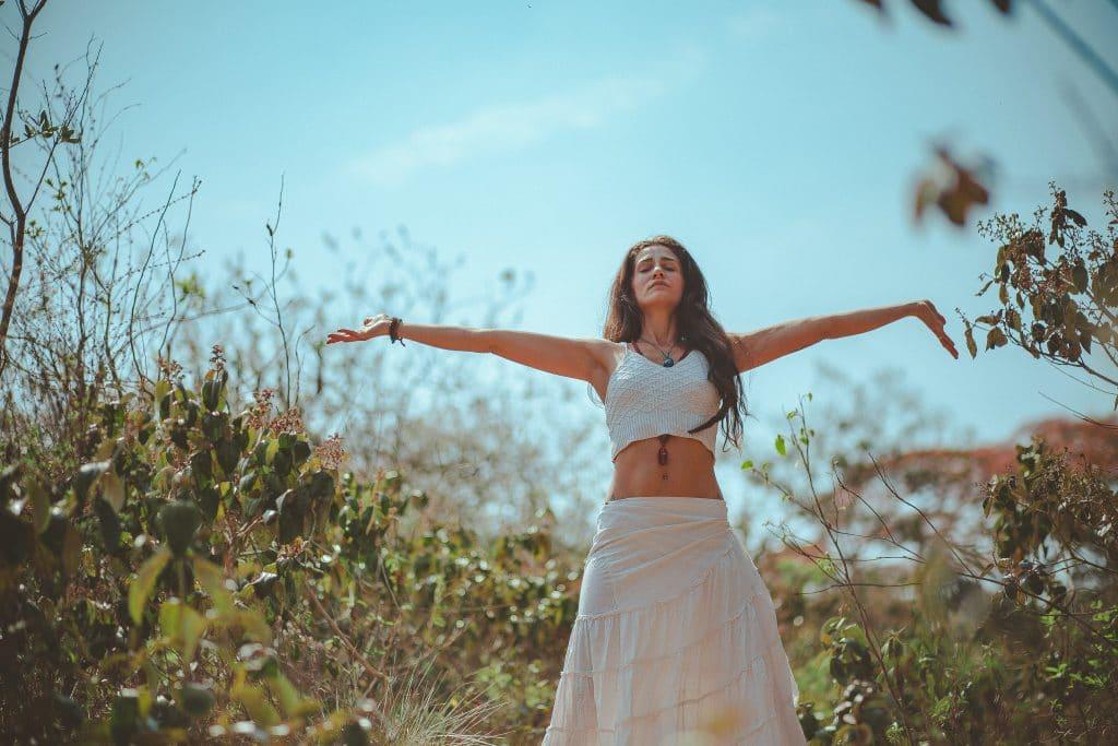 Mulher meditando entre a natureza com braços abertos e olhos fechados
