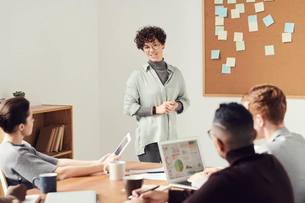 Mulher dando um discurso durante reunião em ambiente de trabalho.