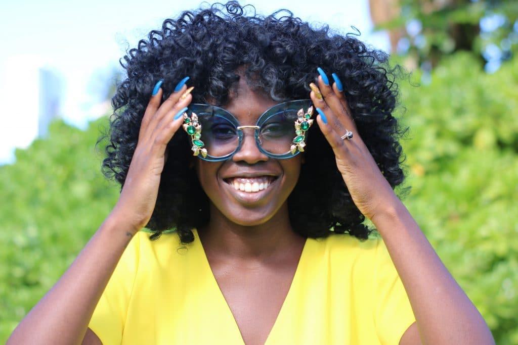 Mulher com mãos no óculos de sol no rosto sorrindo