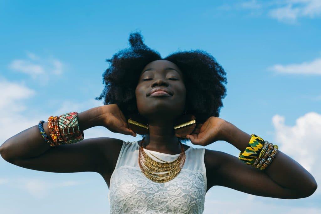 Mulher com mãos atrás das orelhas de olhos fechados com expressão feliz e céu azul ao fundo