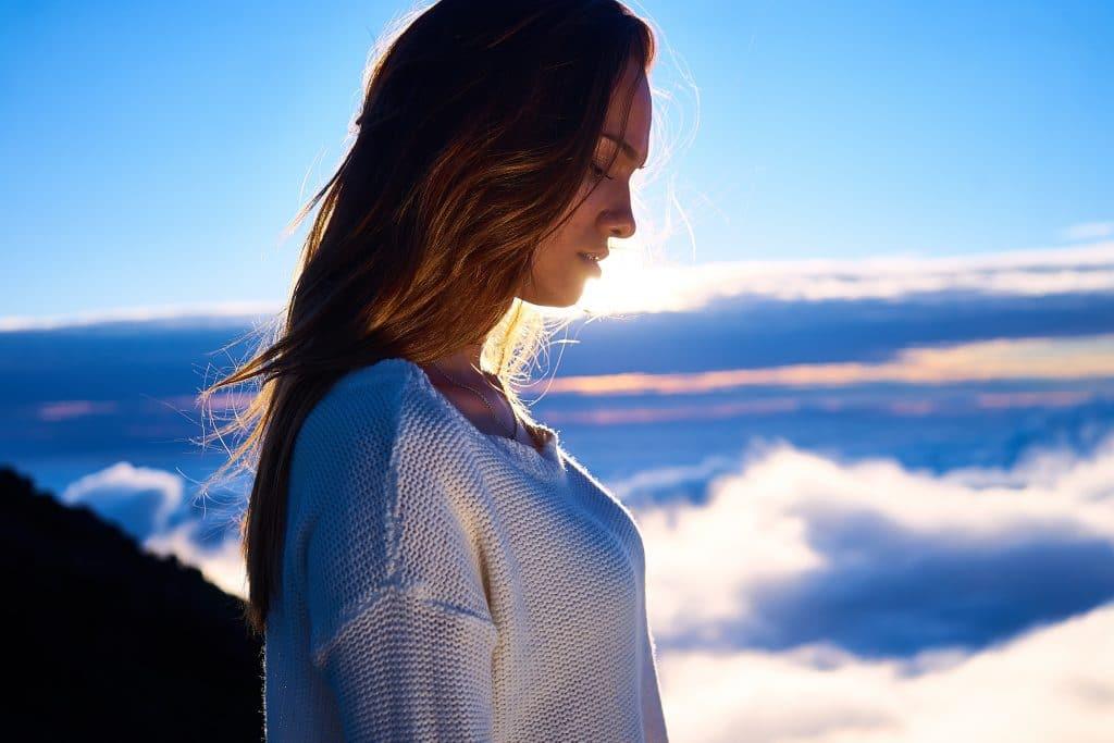 Mulher em pé, de perfil, olhando para baixo. Ao fundo, há uma paisagem com nuvens e a luz do sol.