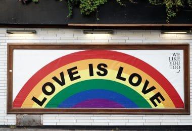 """Parede com um quadro escrito """"love is love""""e um arco iris"""