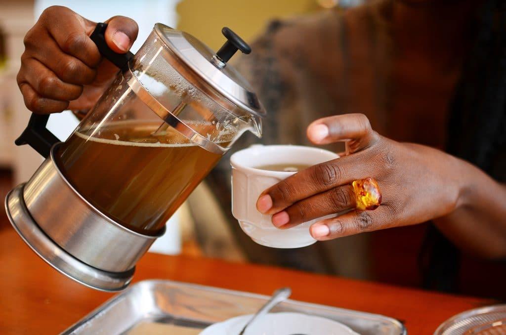 Mulher segurando um bule e xícara de chá