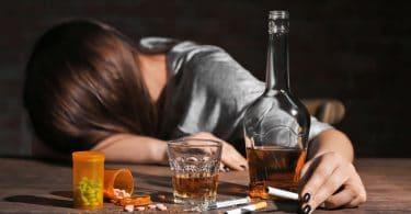 Mulher de cabeça abaixada com mesa com remédios, cigarros e bebida alcoólica