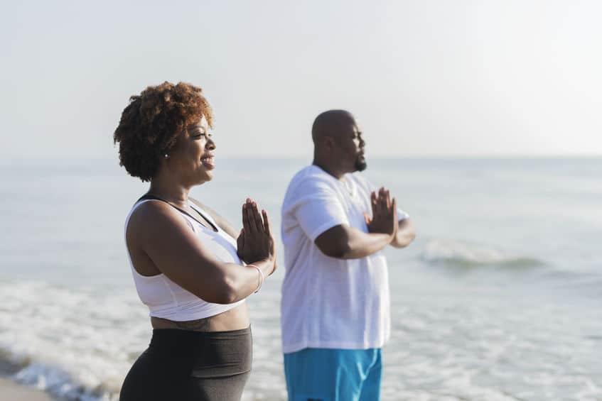 Mulher e homem meditando.