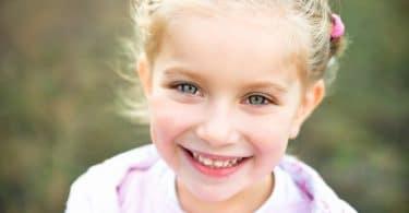 Retrato de menina sorrindo. Ela é loira e está com o cabelo preso, seus olhos são verdes e seus dentes ainda estão nascendo. Atrás dela é possível ver um gramado.