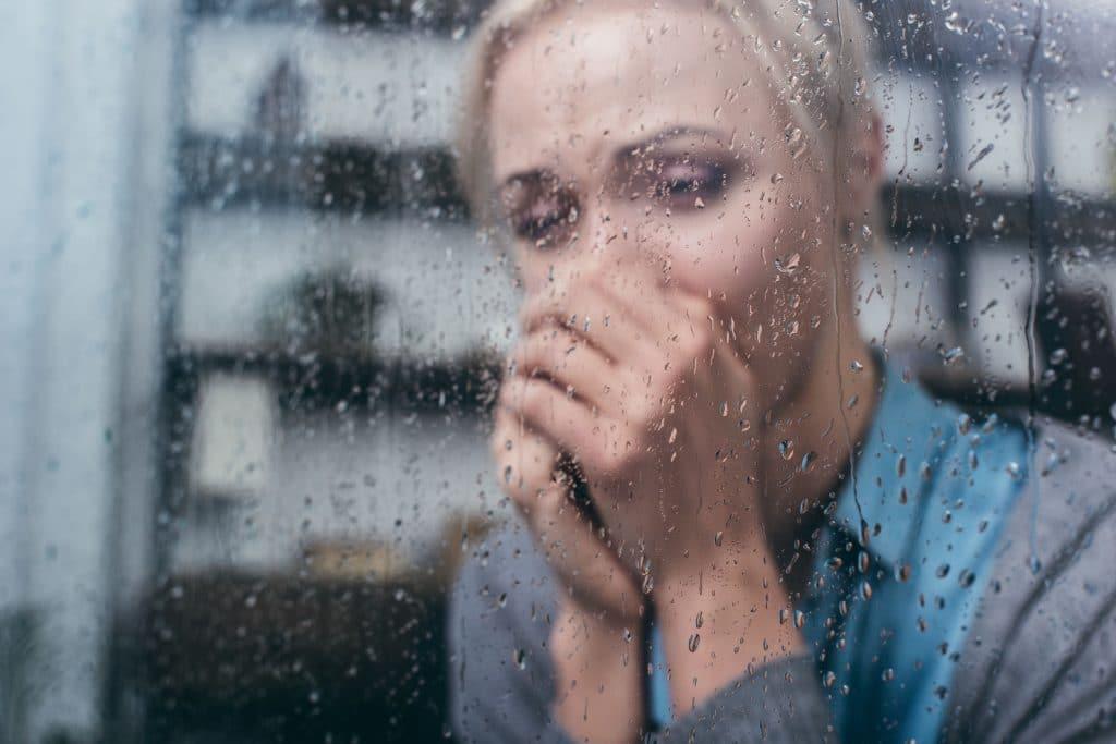 Mulher chorando com as mãos na frente do rosto, de frente para uma janela molhada de chuva.