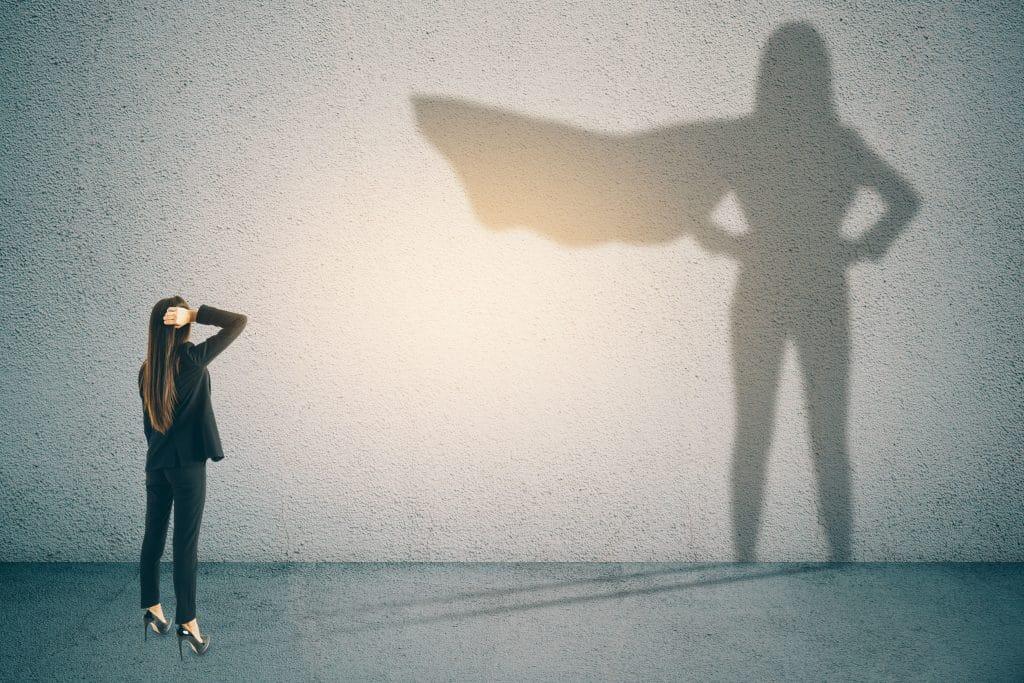 Mulher com traje social, olhando para uma parede branca. Sua sombra a representa como uma heroína, vestindo uma capa, com as mãos na cintura.