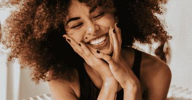 Mulher sorrindo o rosto apoiado nas mãos