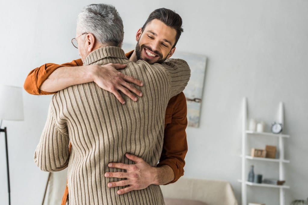 Pai e filho se abraçando na sala da casa