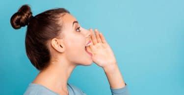 Mulher de perfil com mão no rosto e boca aberta falando