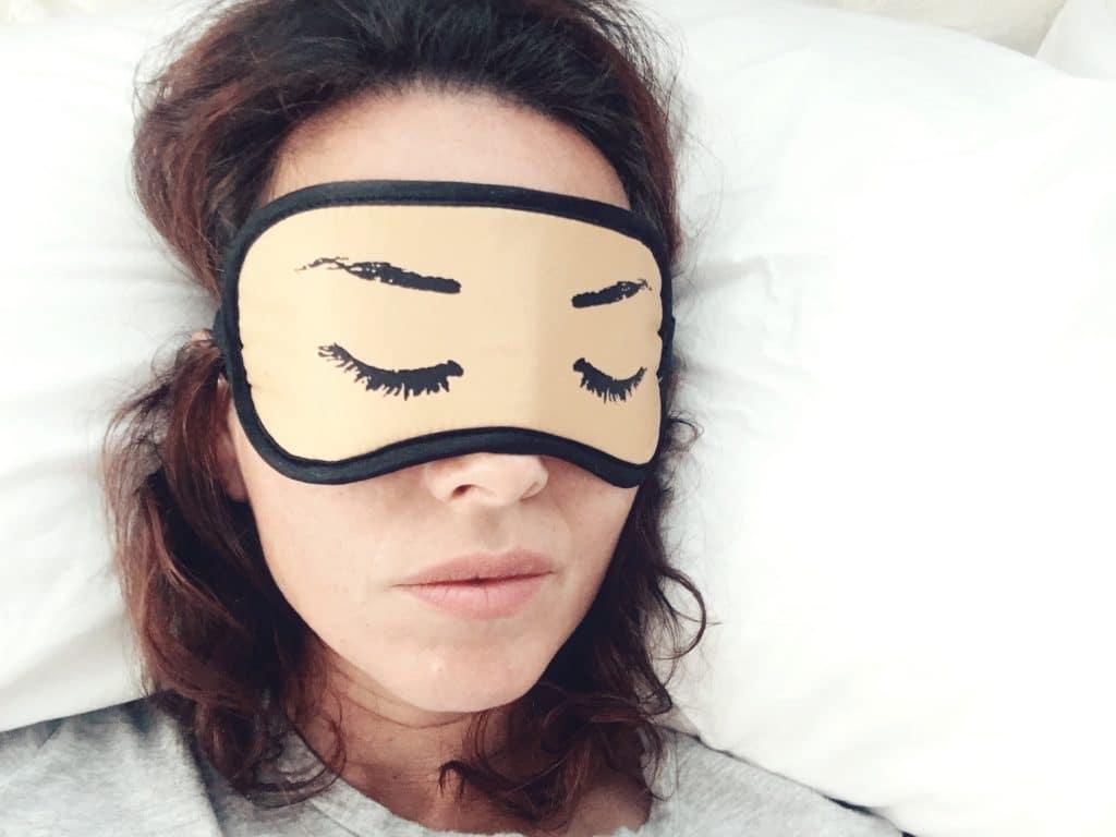 Mulher deitada na cama com uma máscara cobrindo os olhos