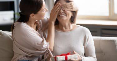 Mulher jovem cobrindo os olhos de uma mulher mais velha, que segura um presente.