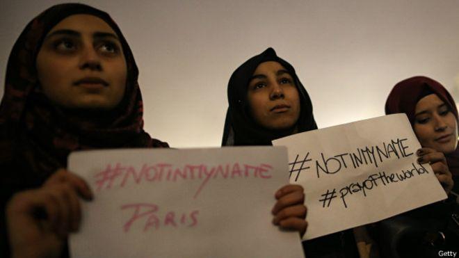 """Mulheres jovens muçulmanas protestam contra ataques terroristas segurando placas om a hashtag """"not in my name"""" (não em meu nome)."""