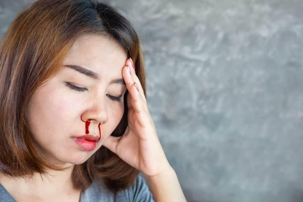 Mulher com o nariz sangrando