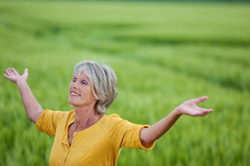 Mulher idosa, feliz, rindo em um parque com os braços abertos