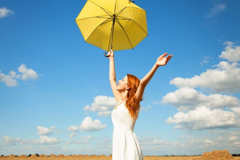 Mulher em campo aberto segurando guarda-chuva amarelo de braços abertos