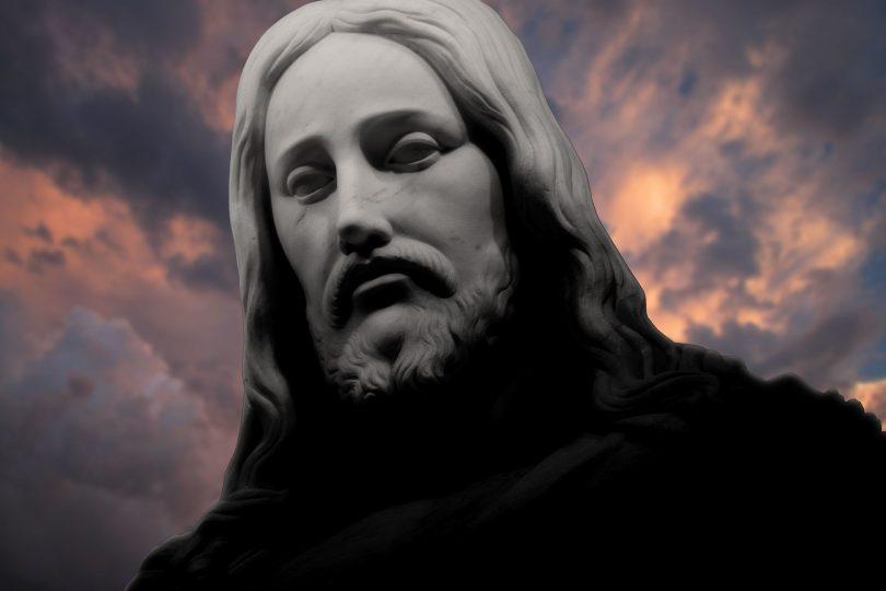 Rosto de estátua de Jesus Cristo, com nuvens escuras encobrindo um céu alaranjado ao fundo.