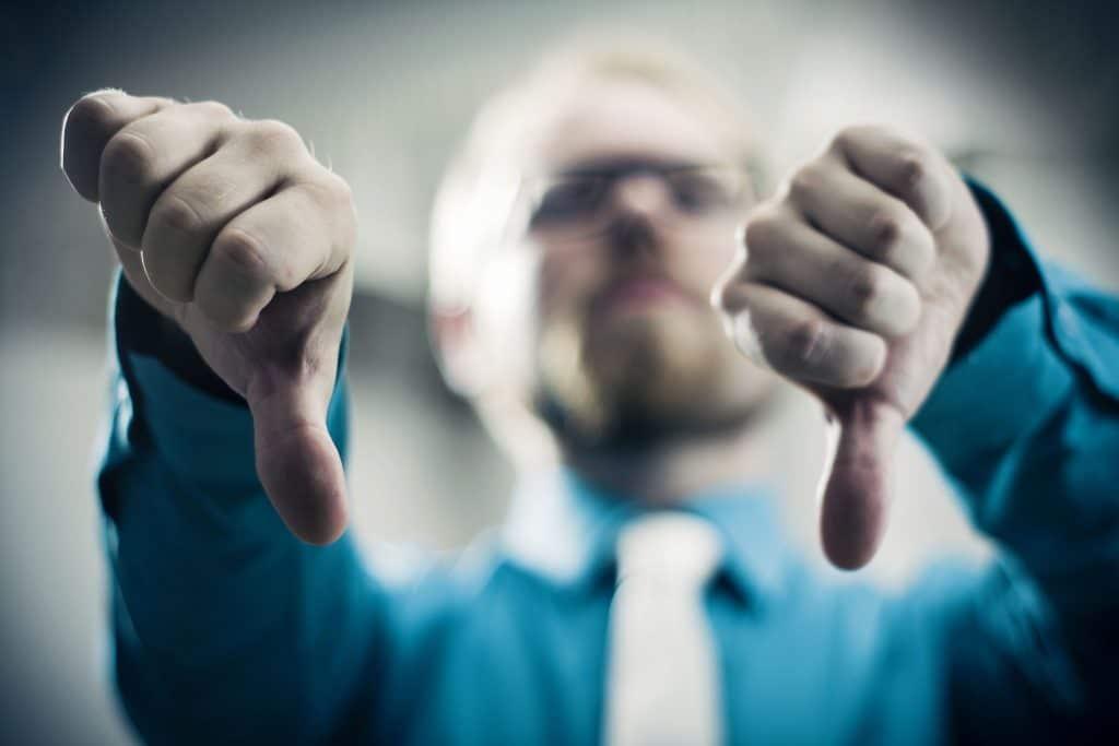 Homem com os dois polegares para baixo