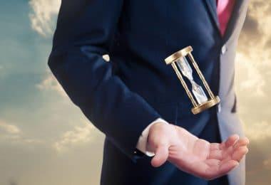 Homem com uma pequena ampulheta sobre sua mão, flutuando. Ele veste terno e gravata.