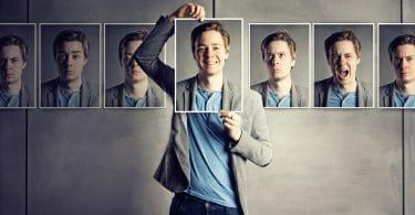 Homem segurando uma foto sorrindo cobrindo seu rosto e atrás diiversas fotos com outras emoções