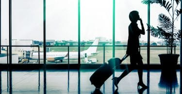 Silhueta de mulher andando em aeroporto, puxando uma mala de rodinhas com uma bolsa apoiada em cima, enquanto fala no celular. Ela está em frente a um vidro onde é possível ver um avião e a pista de pouso e decolagem.