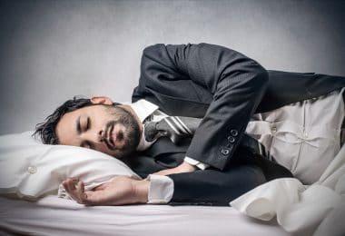 Homem deitado na cama, dormindo, com roupas sociais de trabalho.