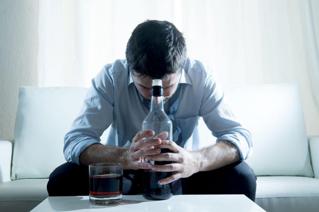 homem sentado em sofá, segurando uma garrafa de bebida com as duas mãos, e com sua cabeça baixa. Ao lado da garrafa, em uma mesinha de centro, está um copo de whisky cheio.