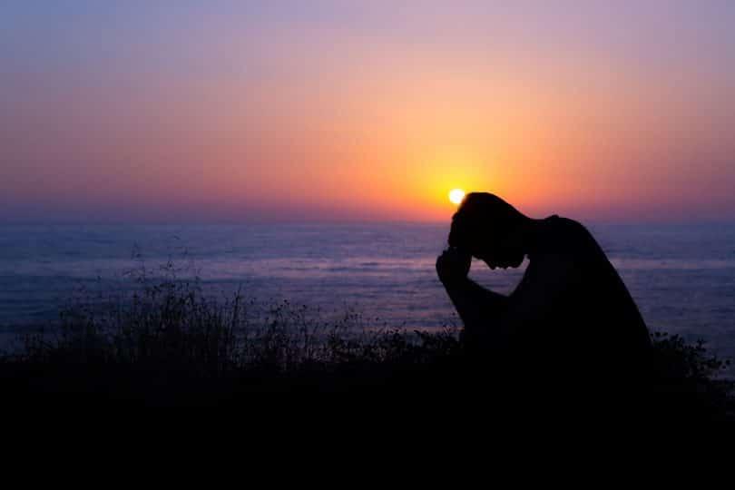 Silhueta de homem ajoelhado com pôr-do-sol ao fundo