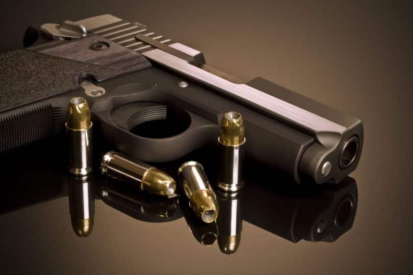 Pistola e balas postas sobre uma mesa.