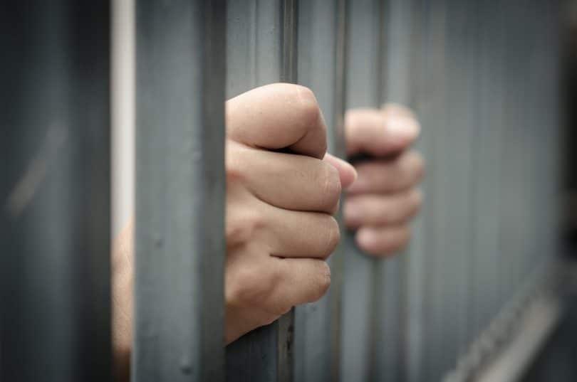 Mãos segurando grades da prisão