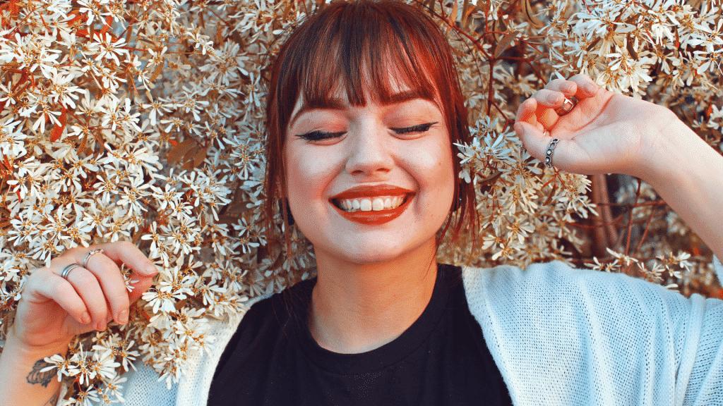 mulher deitada no meio das flores de olhos fechados e sorrindo