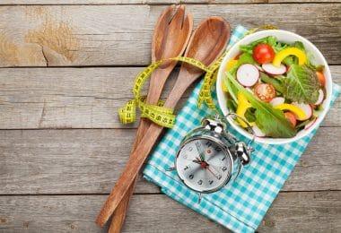 Colheres de pau em cima de uma mesa ao lado de um pote com salada.