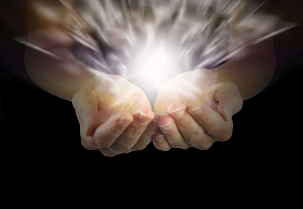 Mãos com as palmas para cima, levemente curvadas, e uma bola de luz sobre elas. A luz representa energia do Reiki.
