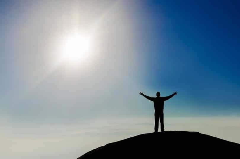Silhueta de homem de costas com braços abertos no topo de montanha com céu azul e sol ao fundo