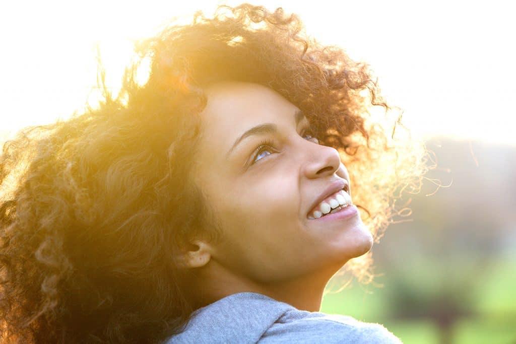 Mulher sorrindo olhando para o céu.