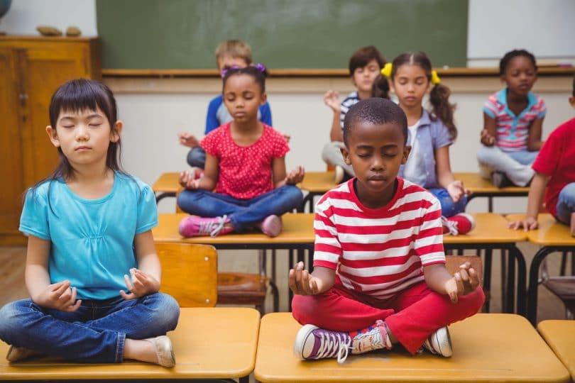 Alunos meditando em posição de lótus na mesa na sala de aula na escola primária