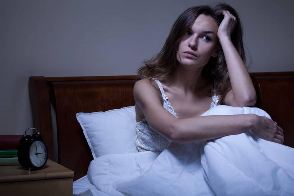 Mulher sentada na cama olhando para o lado sem conseguir dormir