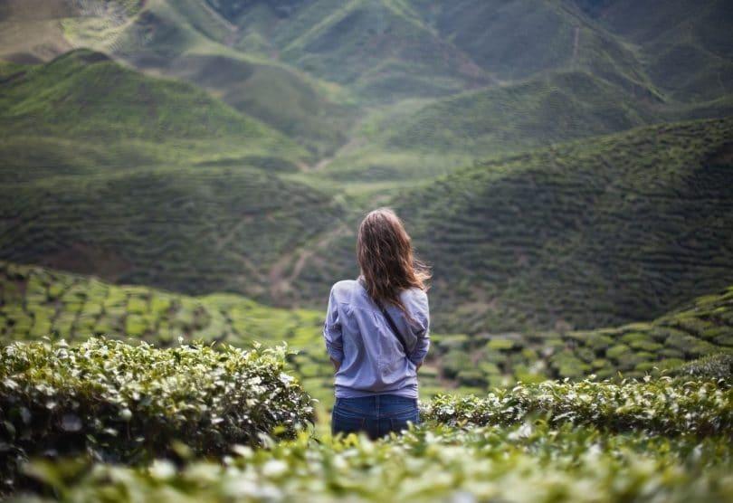 Mulher sozinha, de costas, em meio a paisagem natural montanhosa.