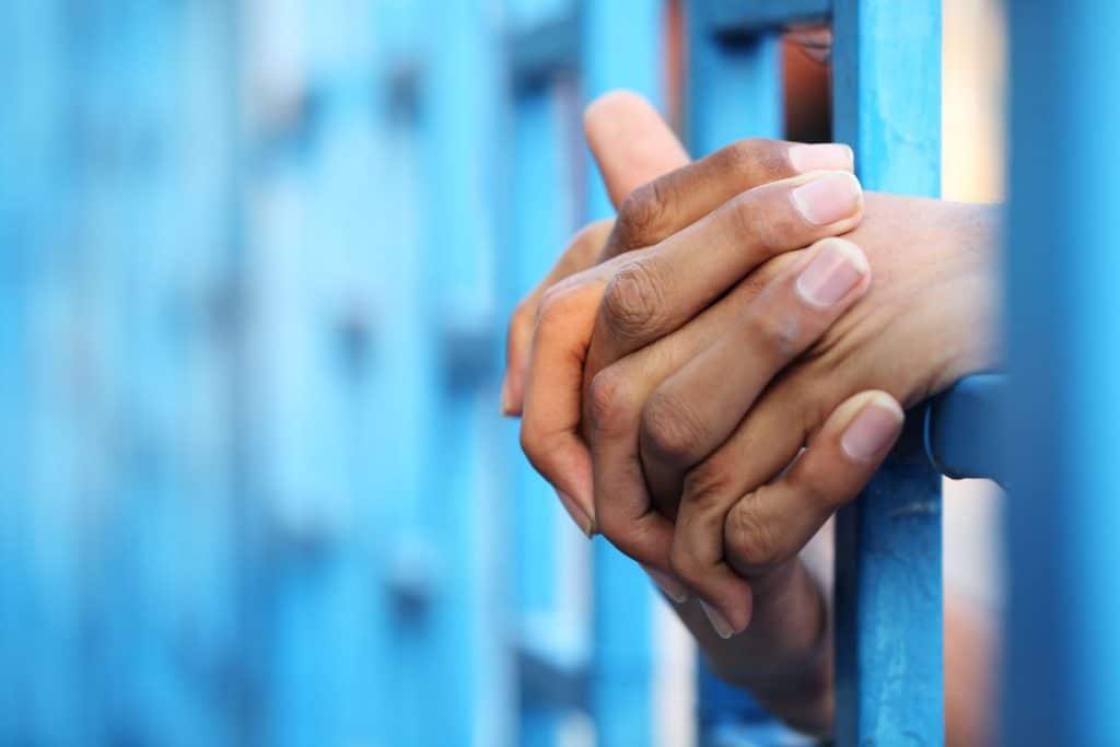 Mãos segurando grade da prisão