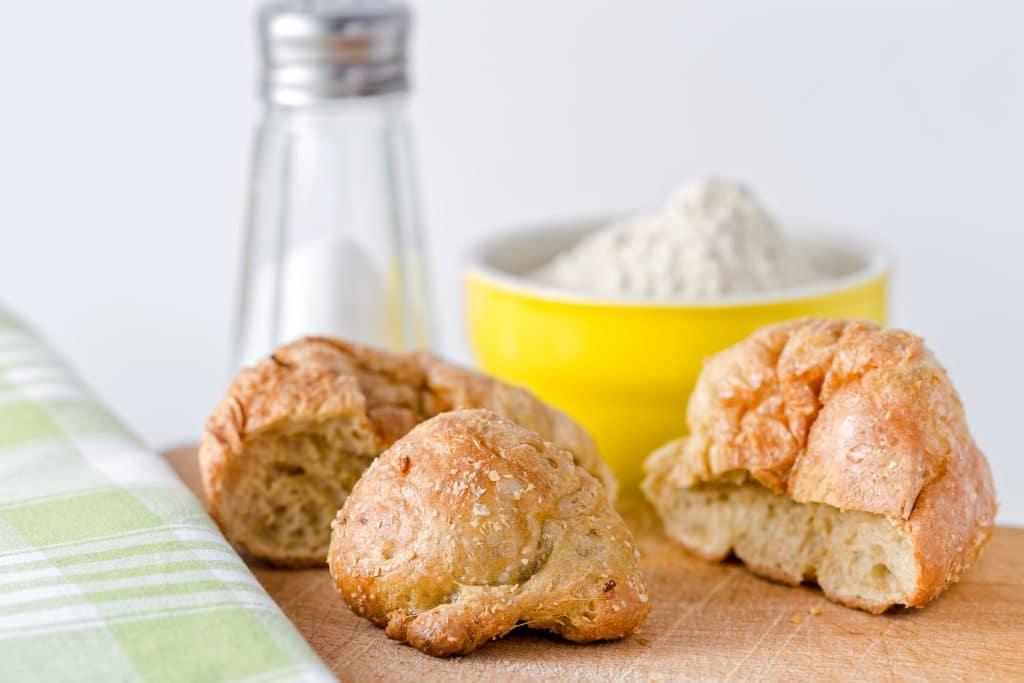 Três pedaços de pão assados, sobre uma mesa de madeira. Ao lado um pote amarelo cheio de farinha branca e um toalha de mesa xadrex nas cores branco e verde. Direitos autorais : Massimiliano Ranauro