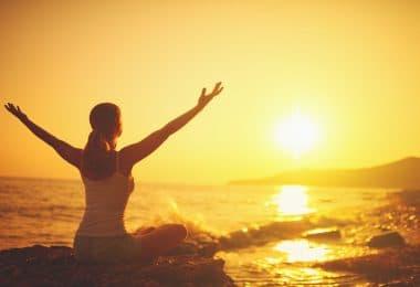 Mulher sentada em pedra numa praia, com os braços abertos, olhando para o pôr do sol.