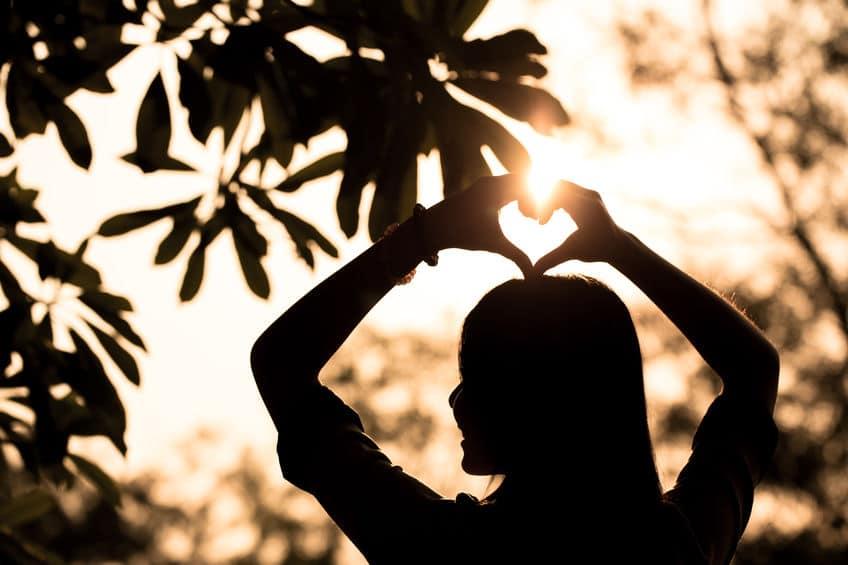 Silhueta de mulher fazendo o formato de um coração com as mãos.