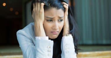 Mulher preocupada com mãos na cabeça sentada