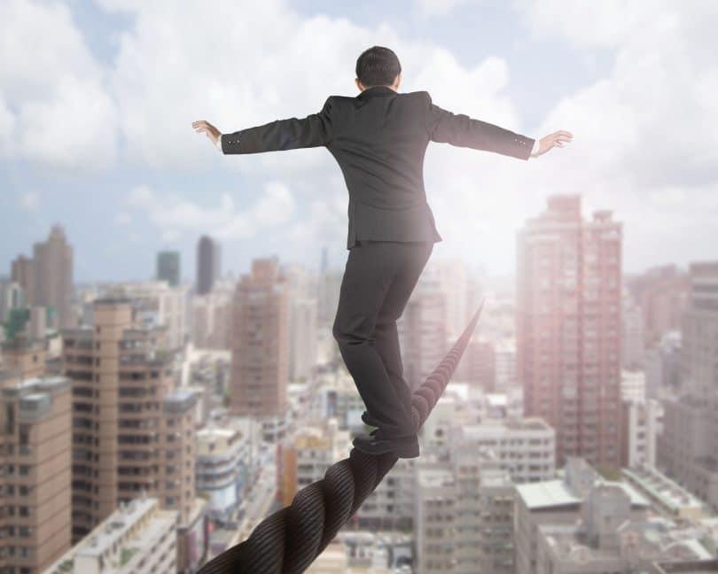 Homem com terno e calça social, se equilibrando em corda, que cruza uma cidade inteira. Ele se equilibra com os braços abertos. Ao fundo, a cidade, com diversos prédios.