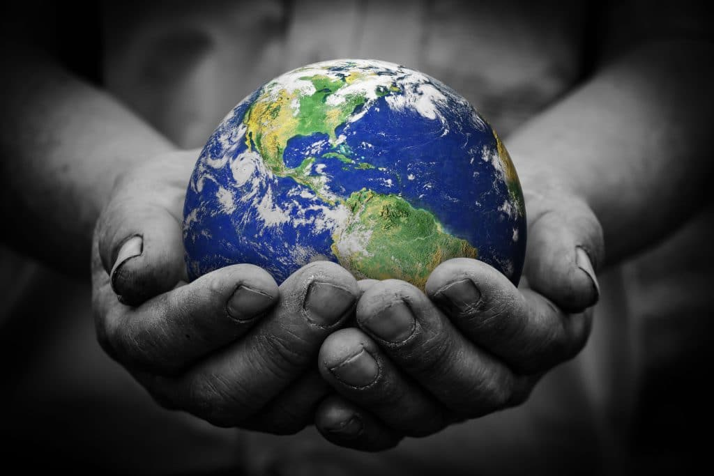 Mãos em preto e branco segurando o planeta Terra.